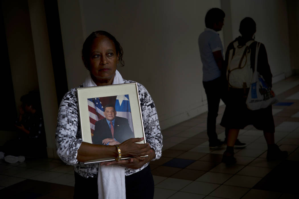 Gloria Rosado Ortiz poses with an image of her late husband, Ernesto Curiel, in San Juan, Puerto Rico, Sept. 4, 2018. Curiel, a 60-year-old who had heart problems and diabetes, walked 10 flights o ...