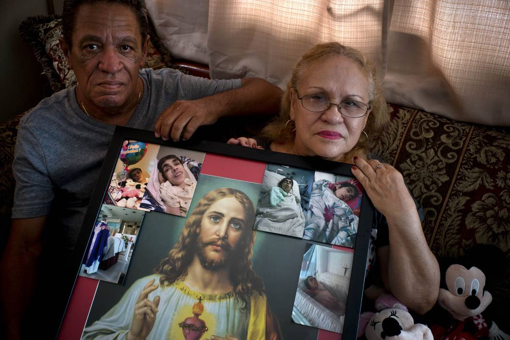 In this Sept. 4, 2018 photo, Maria Gonzalez Munoz, right, and Juan Manuel Gonzalez, pose with an image of Jesus surrounded by photos of her sister Ramona, when she was sick and during her funeral, ...