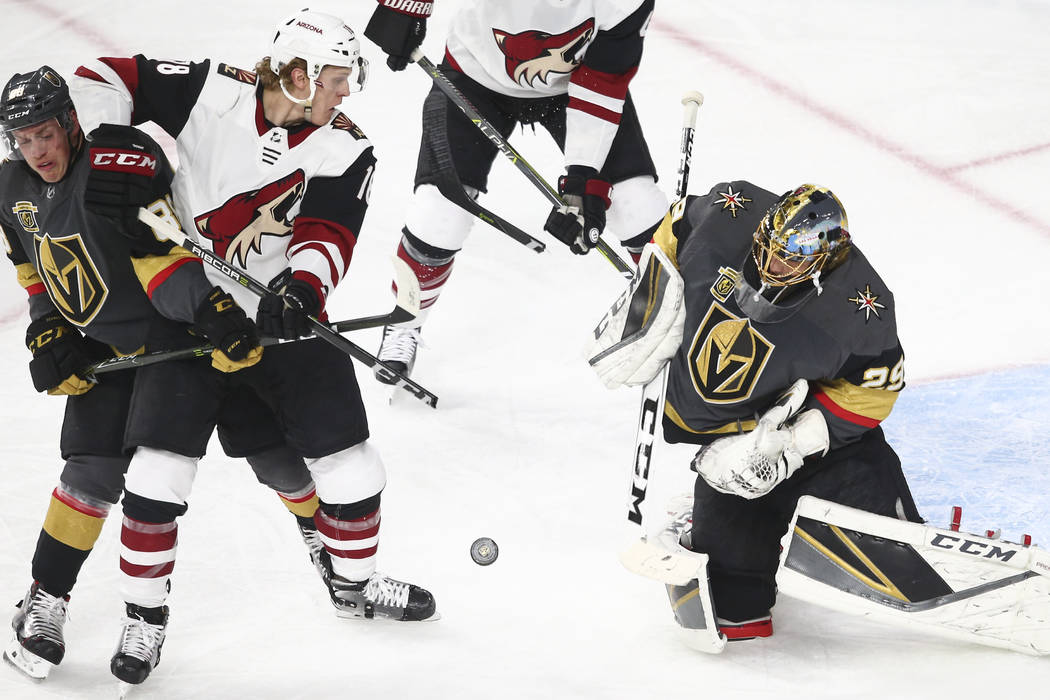 Arizona Coyotes center Christian Dvorak (18) attempts to score as Golden Knights goaltender Marc-Andre Fleury (29) and defenseman Nate Schmidt (88) defend during the first period of an NHL hockey ...