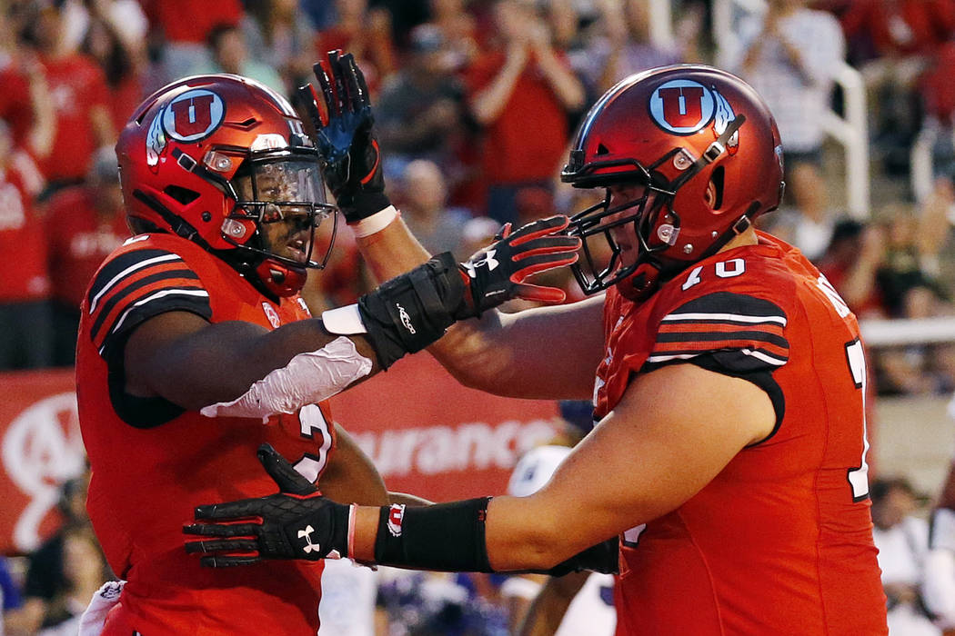 Utah running back Zack Moss, left, celebrates after scoring with teammate Jackson Barton, right, in the second half of an NCAA college football game against Weber State Thursday, Aug. 30, 2018, in ...