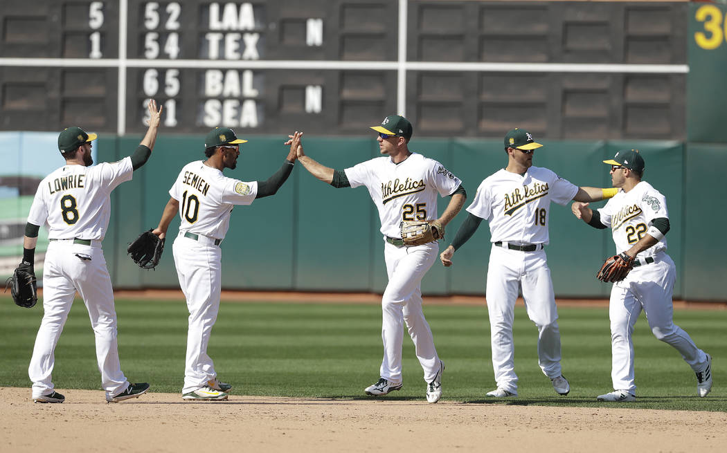 Oakland Athletics' Jed Lowrie, from left, Marcus Semien, Stephen Piscotty, Chad Pinder and Ramon Laureano celebrate after beat the New York Yankees in a baseball game in Oakland, Calif., Monday, S ...