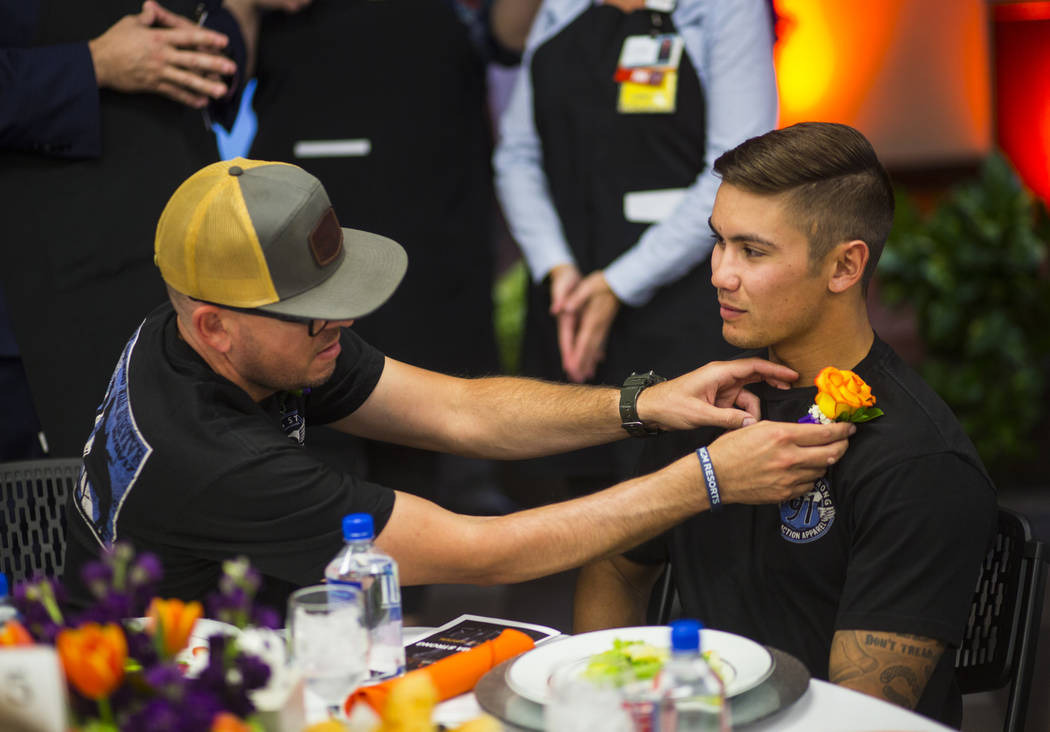San Bernardino County firefighter Mike Kordich, left, who was shot while saving concertgoers, adjusts the boutineer of fellow firefighter and Oct. 1 survivor David Arnold at Sunrise Hospital and M ...
