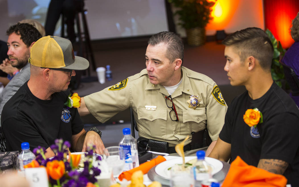 Andrew Walsh, deputy chief of tourist safety at the Las Vegas Metropolitan Police Department, center, talks with San Bernardino County firefighters and Oct. 1 survivors Mike Kordich, left, and Dav ...