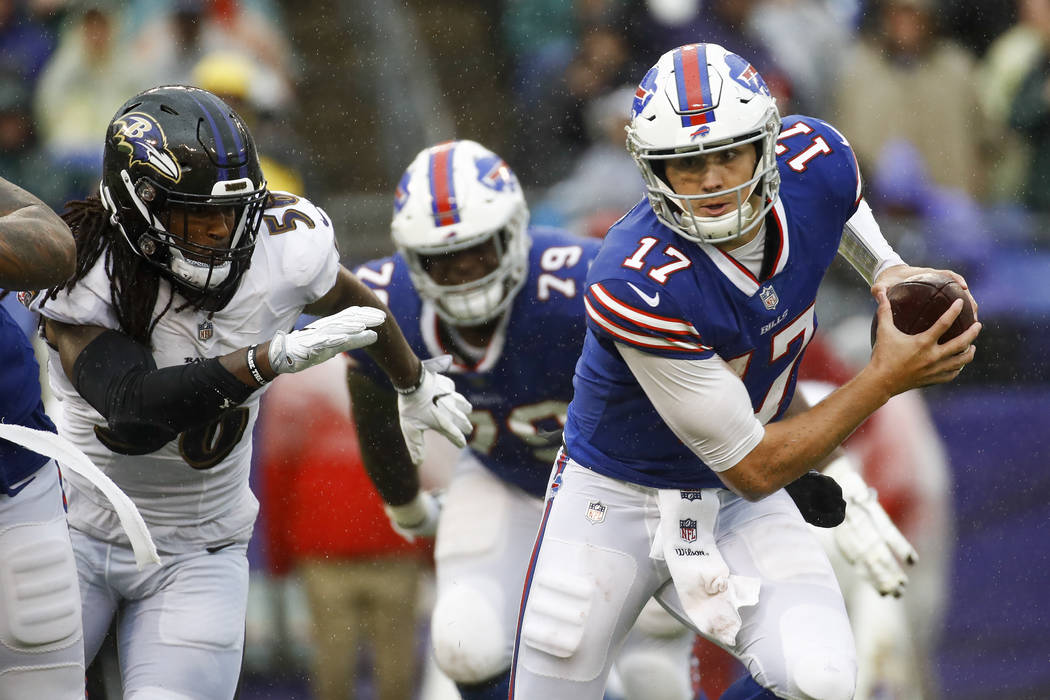 Buffalo Bills quarterback Josh Allen (17) scrambles away from Baltimore Ravens linebacker Tim Williams (56) with the ball during the second half of an NFL football game, Sunday, Sept. 9, 2018, in ...