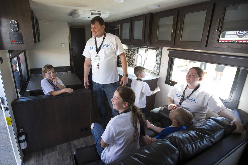 Jared,standing, and Tera Stacey, far right, and their children walk through their new travel trailer they received courtesy of the Make-A-Wish Southern Nevada ahead of the South Point 400 NASCAR C ...