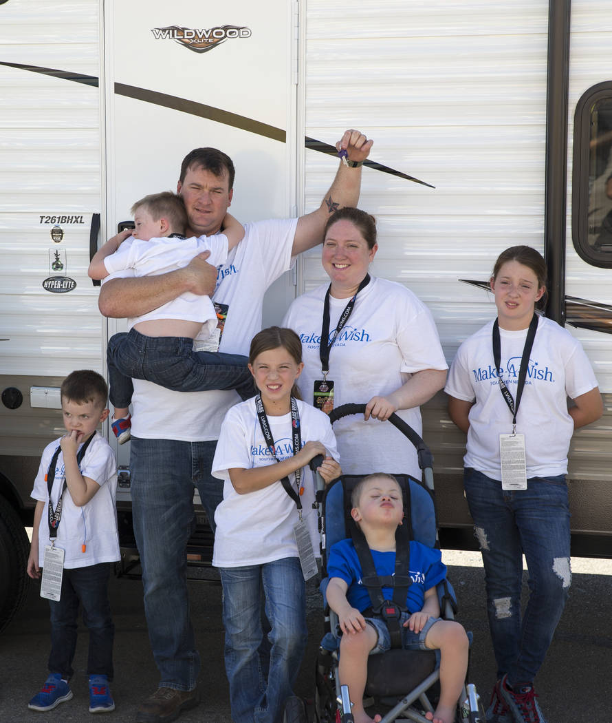 Jared,ʴhird left, holds a key to the travel trailer with Tera Stacey, center, and their children including Andrew, 5, sitting in the wheelchair, outside their new travel trailer they receive ...