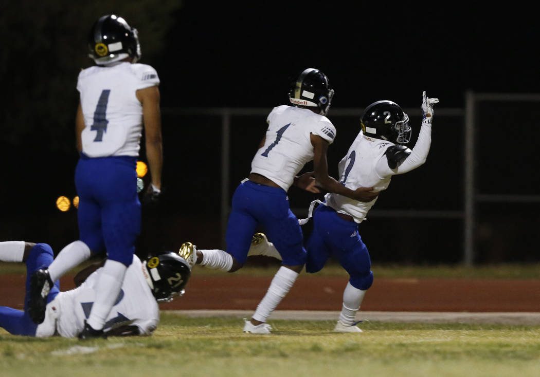 Desert Pines' Tye Moore, right, celebrates his touchdown with his teammates including Tyler Williamson (1) and Branden Thomas (4) during the first half of a football game at Sierra Vista High Scho ...