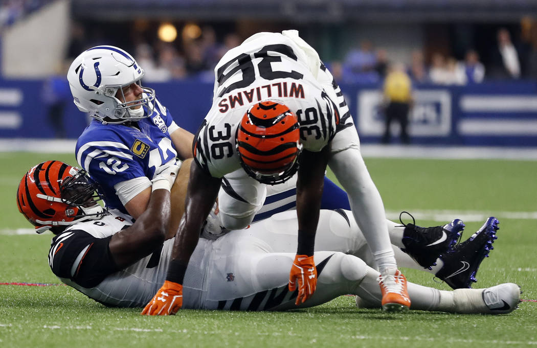Indianapolis Colts quarterback Andrew Luck (12) is tackled by Cincinnati Bengals defensive end Michael Johnson (90) and defensive back Shawn Williams (36) during the first half of an NFL football ...