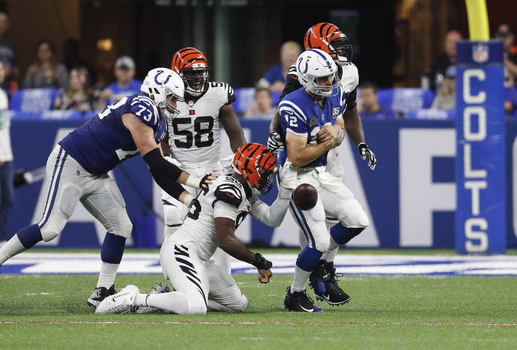 Cincinnati Bengals defensive end Carlos Dunlap (96) strips the back from Indianapolis Colts quarterback Andrew Luck (12) during the second half of an NFL football game in Indianapolis, Sunday, Sep ...