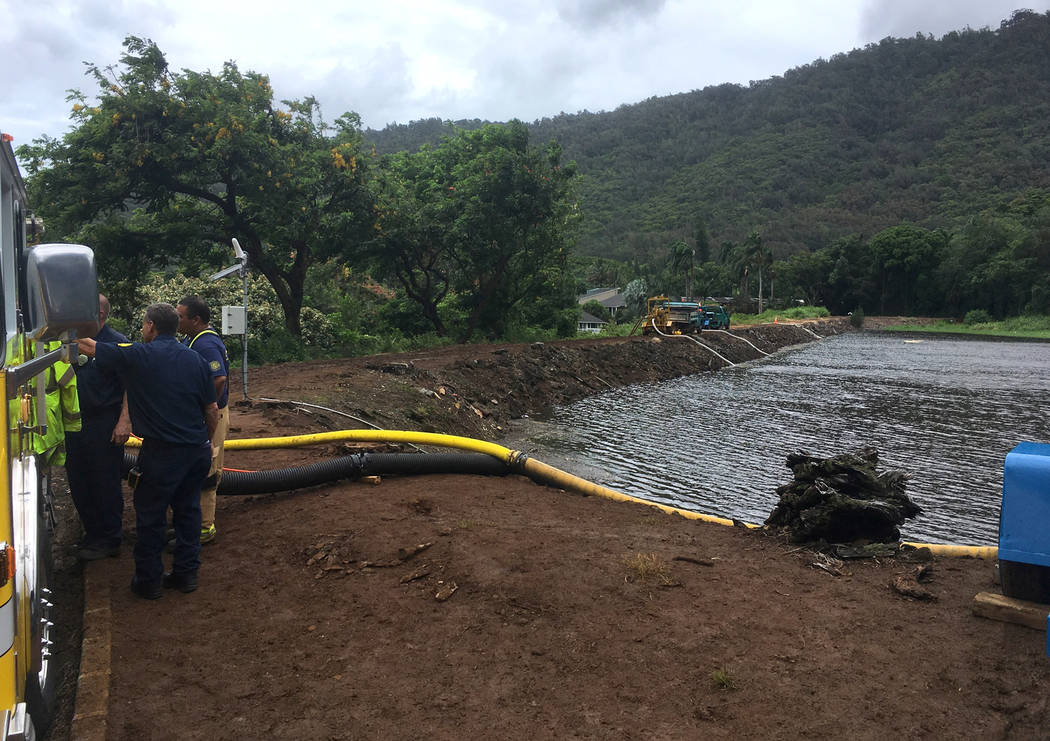 Officials pump water from a reservoir where a dam came close to overflowing in Honolulu on Thursday, Sept. 13, 2018. Honolulu officials say they may need to evacuate 10,000 people from a residenti ...