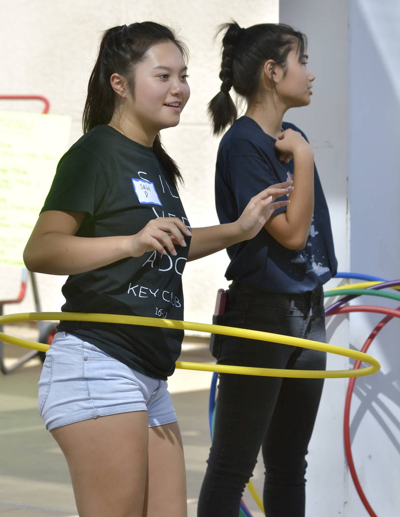 Sage Dang, 17, left, uses a hula hoop while waiting for people to engage in a game involving the hoops during the 28th Annual Pacific Islander Festival and Hoկlauleա at the Henderson E ...