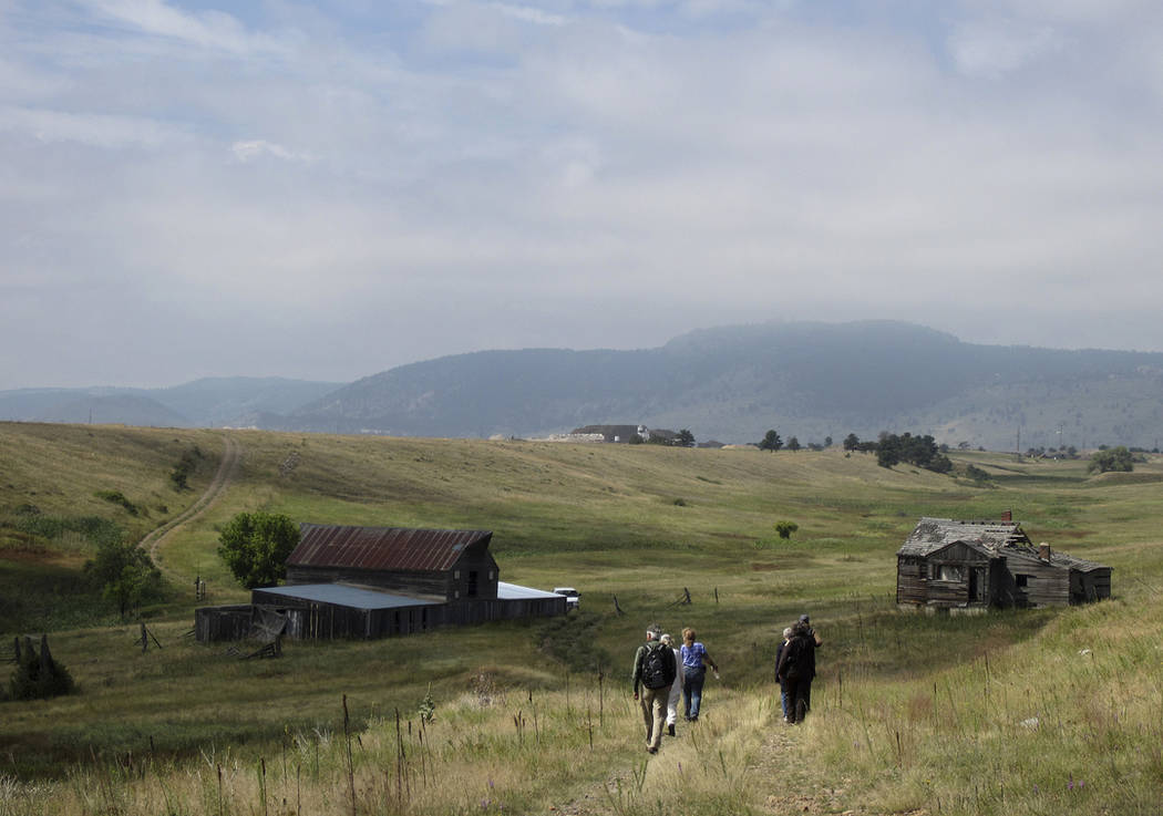Visitors approach a former ranch house and barn during a guided hike on the Rocky Flats National Wildlife Refuge near Denver in 2017. (AP Photo/Dan Elliott)