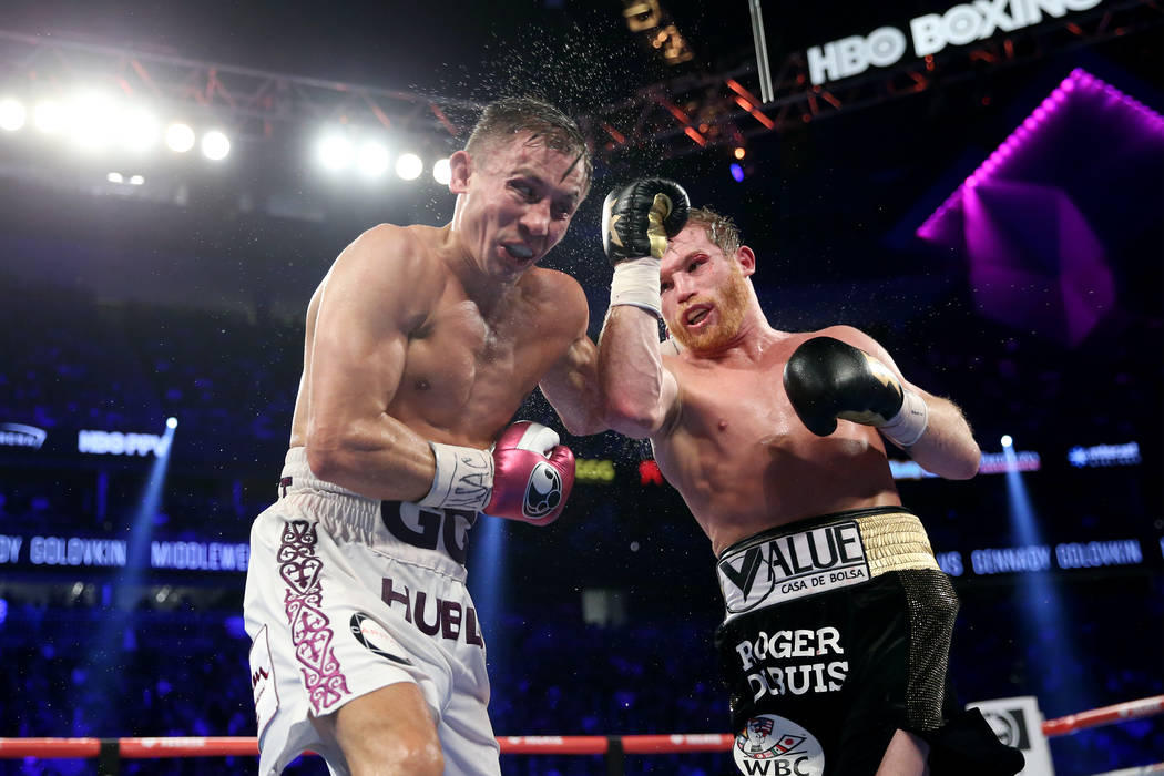 """Saul """"Canelo"""" Alvarez, right, connects a punch against Gennady Golovkin in the WBC, WBA, IBO, RING middleweight title bout at T-Mobile Arena in Las Vegas, Saturday, Sept. 15, 2018. Alvar ..."""