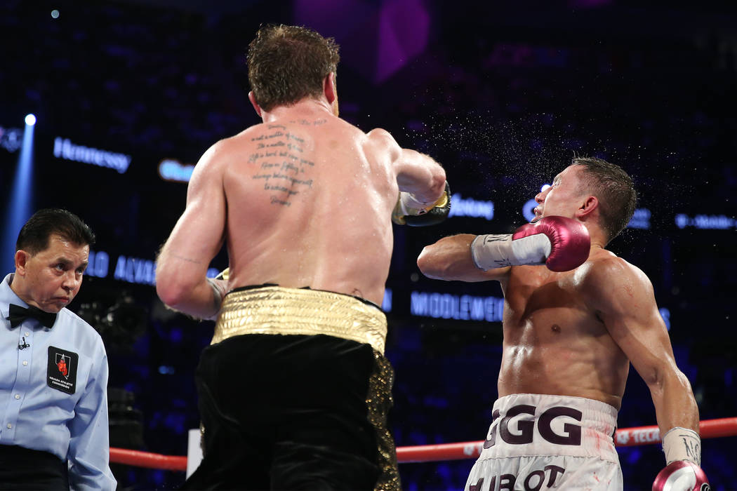 """Saul """"Canelo"""" Alvarez, left, connects a punch against Gennady Golovkin in the WBC, WBA, IBO, RING middleweight title bout at T-Mobile Arena in Las Vegas, Saturday, Sept. 15, 2018. Alvare ..."""