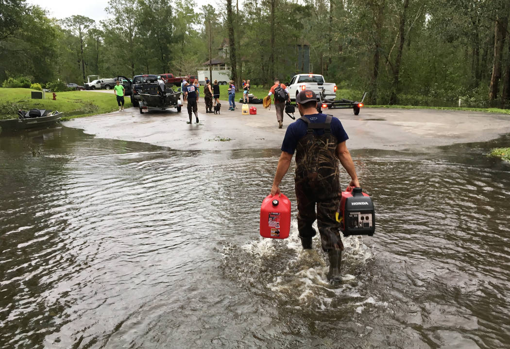 Kevin Knox carries gas and a generator after being rescued from his flooded neighborhood from the effects of Florence, now a tropical storm, in New Bern, N.C., on Saturday, Sept. 15, 2018. (AP Pho ...