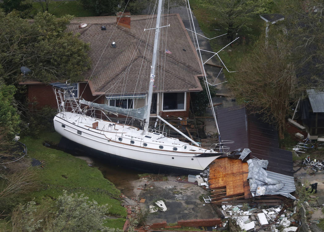 A sailboat is shoved up against a house and a collapsed garage Saturday, Sept. 15, 2018, after heavy wind and rain from Florence, now a tropical storm, blew through New Bern, N.C. (AP Photo/Steve ...