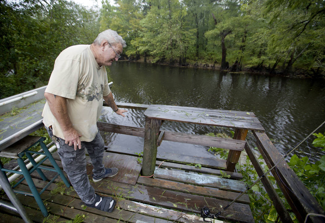 Bennie Todd shows how high the Lumber River rose during Hurricane Matthew two years in his backyard in Lumberton, N.C., Friday, Sept. 14, 2018. Now the town is bracing for another potentially cata ...