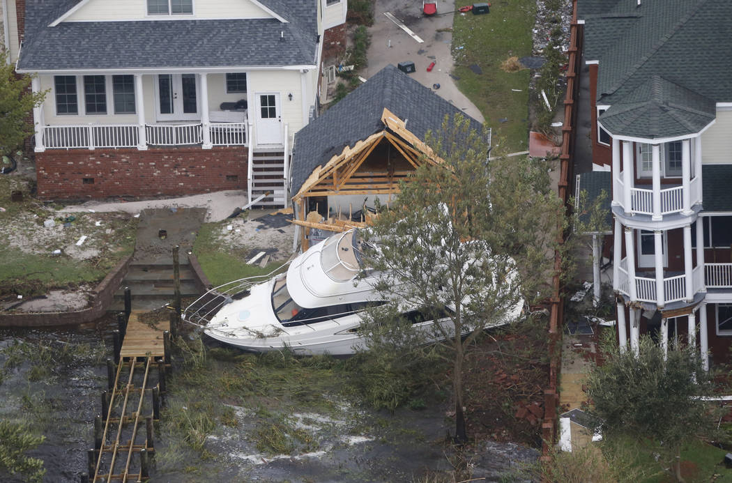 A yacht sits on the Neuse river bank in between buildings after hurricane Florence passed through the area in New Bern, NC., Saturday, Sept. 15, 2018. (AP Photo/Steve Helber)