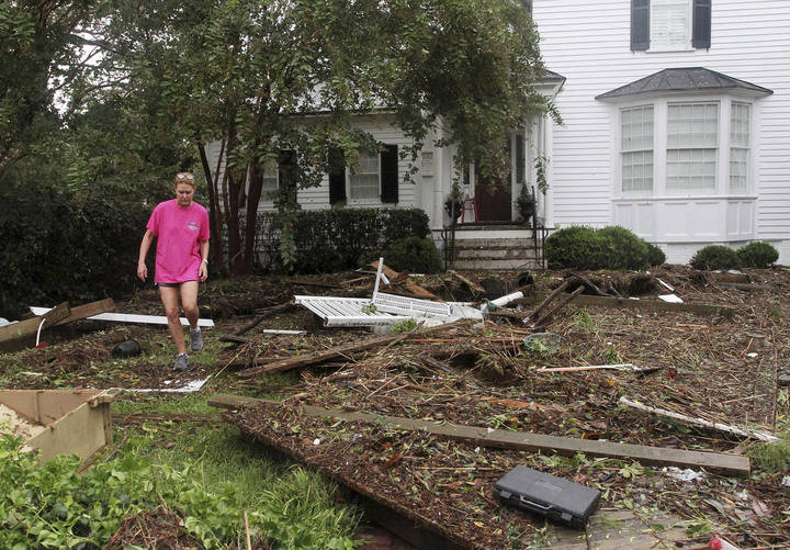 Resident Alice Tolson steps over storm debris that washed up from the Neuse River at her home on East Front Street in New Bern, N.C., Saturday, Sept. 15, 2018, after Hurricane Florence sweeps over ...