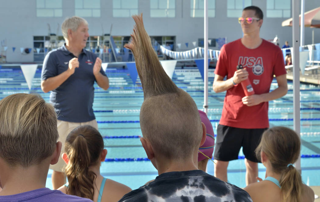 Duncan McClaren, 10, center, and Zane Grothe, right, listen as Boulder City Henderson Heatwave Swim Team head coach Mike Polk, left, speaks during a swimming clinic at the Henderson Multigeneratio ...