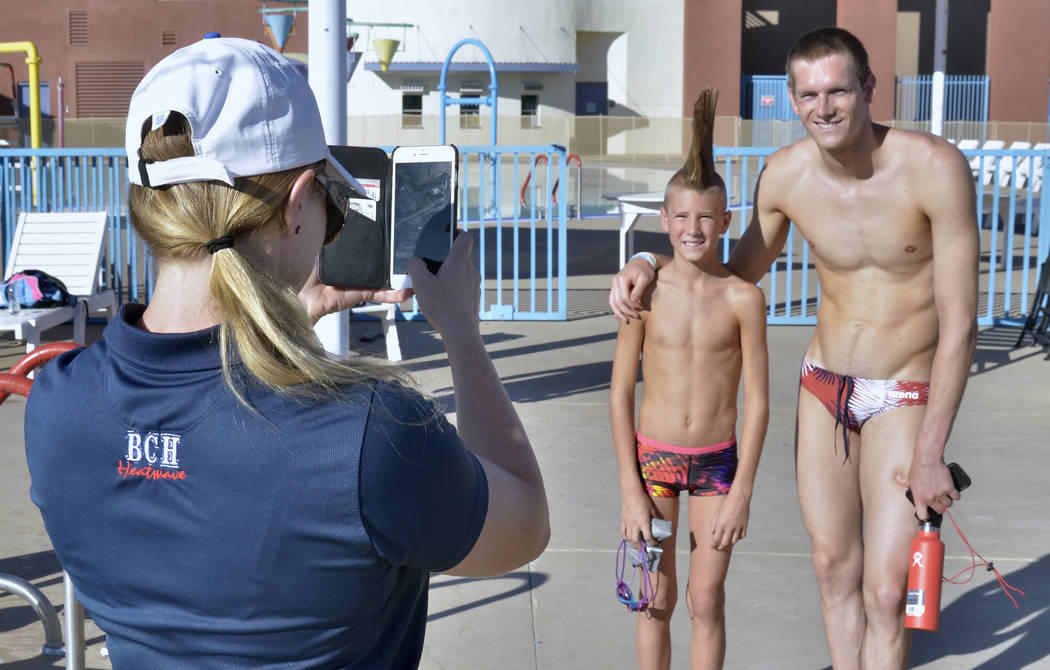 Boulder City Henderson Heatwave Swim Team coach Sarah Fecteau, left, takes a picture of Duncan McClaren, 10, center, with Zane Grothe before a swimming clinic headed by Grothe at the Henderson Mul ...