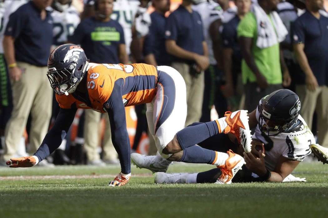 Denver Broncos linebacker Von Miller hauls down Seattle Seahawks quarterback Russell Wilson (3) for a sack during the second half of an NFL football game Sunday, Sept. 9, 2018, in Denver. (AP Phot ...