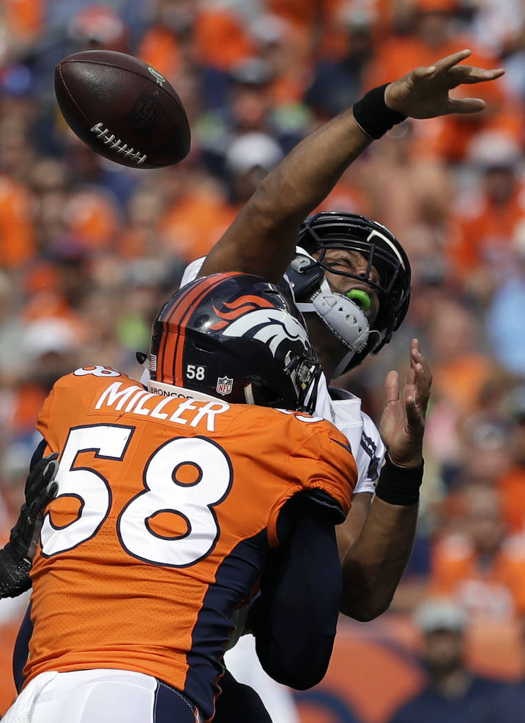FILE - In this Sept. 9, 2018, file photo, Seattle Seahawks quarterback Russell Wilson, top, loses the ball as he is hit by Denver Broncos linebacker Von Miller (58) during the first half of an NFL ...