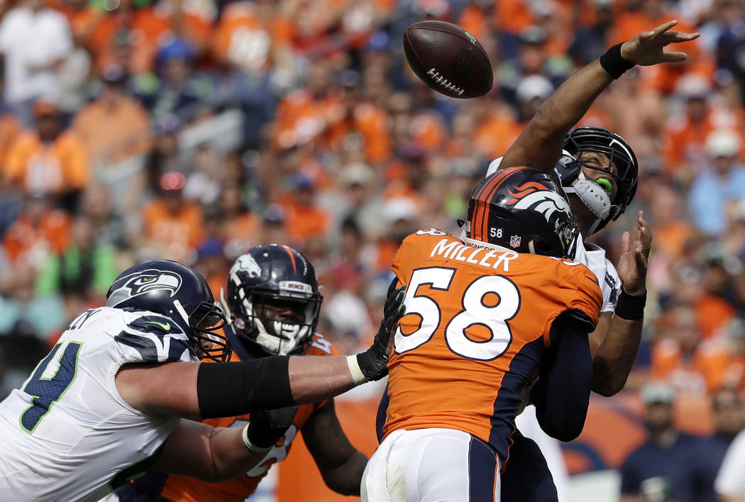 FILE - In this Sunday, Sept. 9, 2018, file photo, Seattle Seahawks quarterback Russell Wilson loses the ball as he is hit by Denver Broncos linebacker Von Miller (58) during the first half of an N ...