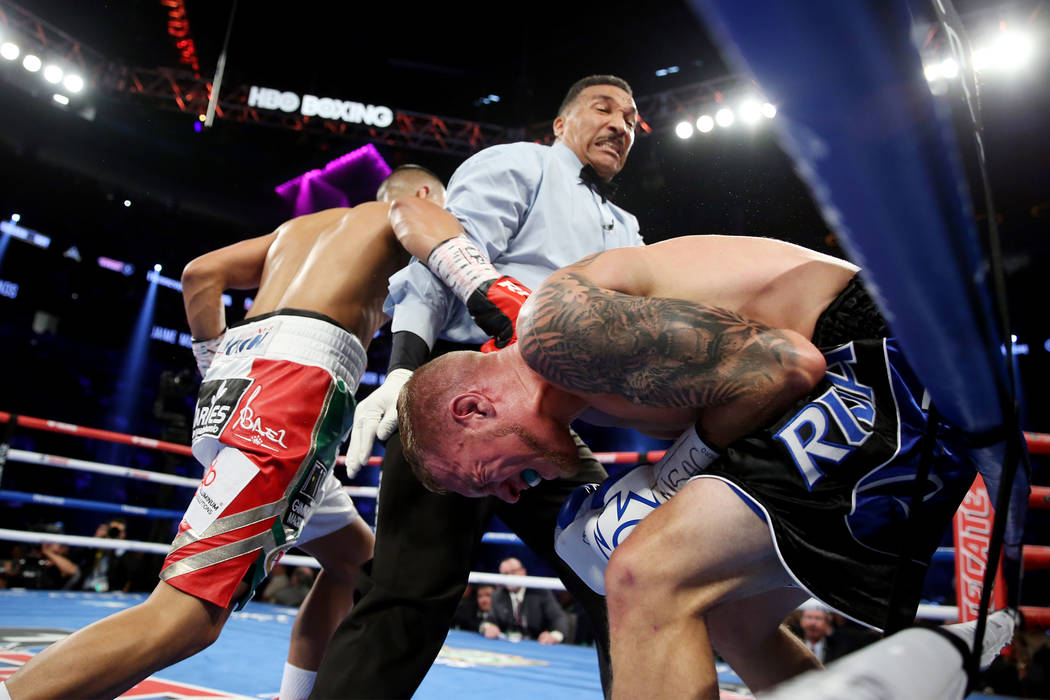 Referee Tony Weeks, center, steps in to stop the fight between Jaime Munguia, left, and Brandon Cook in the WBO middleweight title bout at T-Mobile Arena in Las Vegas, Saturday, Sept. 15, 2018. Mu ...