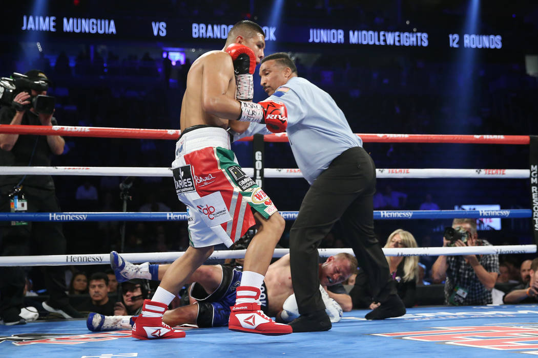 Jaime Munguia turns to his corner after knocking down Brandon Cook in the third round of the WBO middleweight title bout at T-Mobile Arena in Las Vegas, Saturday, Sept. 15, 2018. Munguia won by wa ...