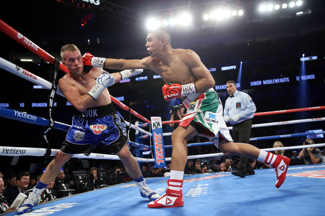 Jaime Munguia, right, throws a punch against Brandon Cook in the WBO middleweight title bout at T-Mobile Arena in Las Vegas, Saturday, Sept. 15, 2018. Munguia won by way of technical knockout in t ...
