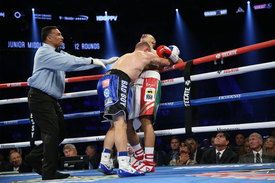 Brandon Cook, center, pushes Jaime Munguia as referee Tony Weeks steps in to break up in the WBO middleweight title bout at T-Mobile Arena in Las Vegas, Saturday, Sept. 15, 2018. Munguia won by wa ...