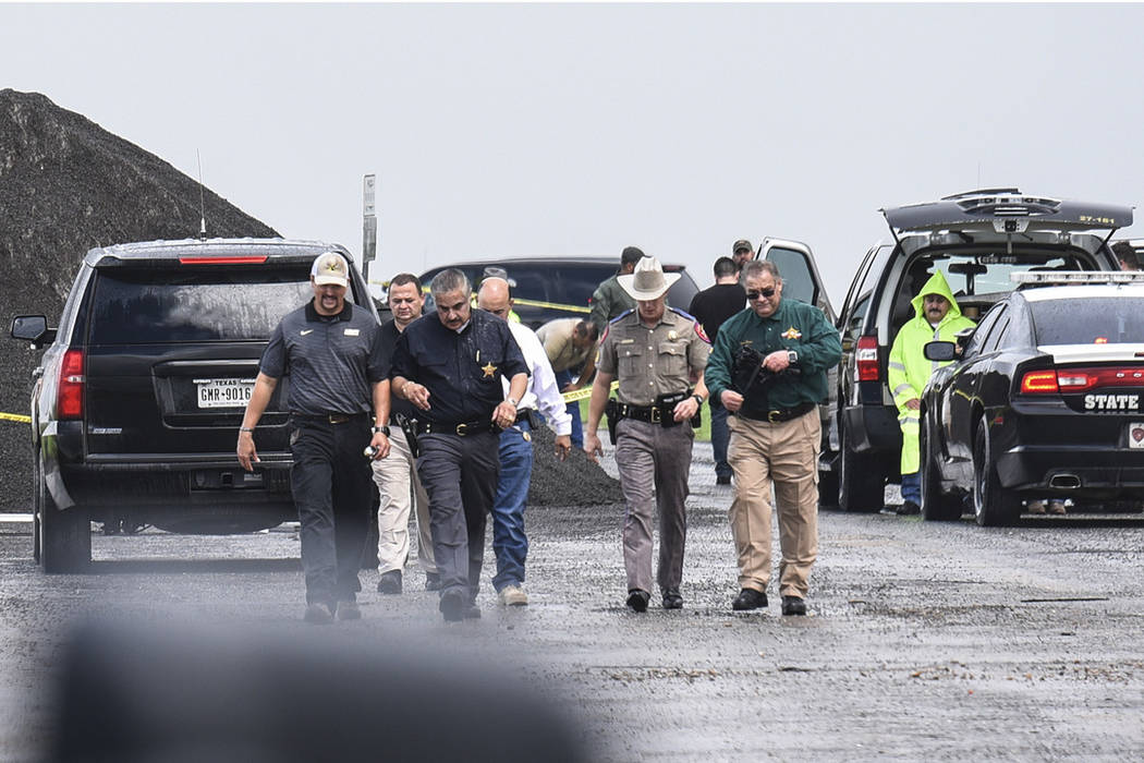 Law enforcement officers gather near the scene where the body of a woman was found near Interstate 35 north of Laredo, Texas on Saturday, Sept. 15, 2018. (Danny Zaragoza/The Laredo Morning Times v ...