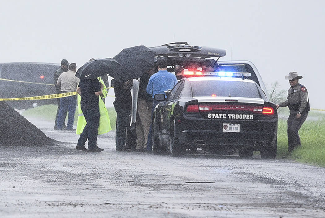 Law enforcement officers gather near the scene where the body of a woman was found near Interstate 35 north of Laredo, Texas on Saturday, Sept. 15, 2018. (Danny Zaragoza/The Laredo Morning Times ...