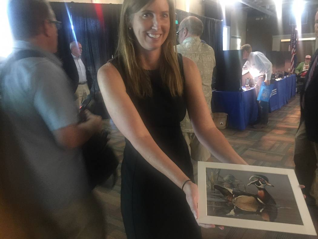 Andrea Travnicek, the Department of Interior's acting assistant secretary for fish, wildlife and parks, displays the winner of the Federal Duck Stamp Art Contest on Saturday, Sept. 15, 2018, at ...
