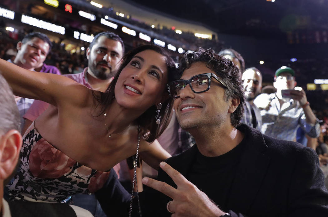 Actor Jaime Camil, right, poses for a photo with a fan before a middleweight title boxing match between Canelo Alvarez and Gennady Golovkin, Saturday, Sept. 15, 2018, in Las Vegas. (AP Photo/Isaac ...