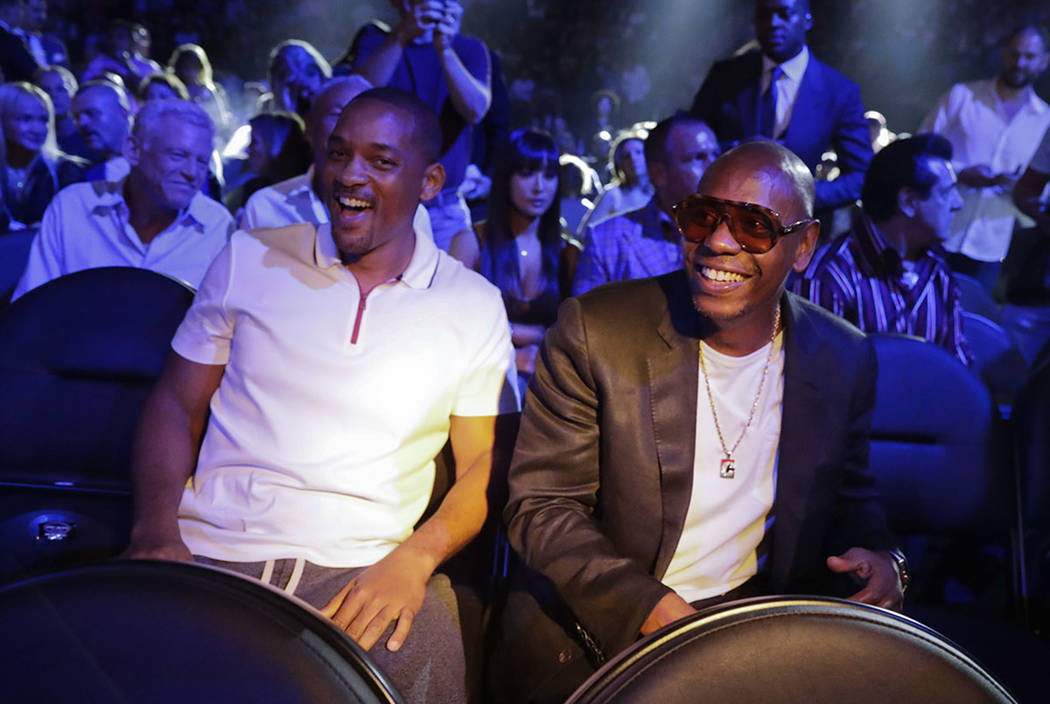 Will Smith, left, and Dave Chapelle wait for the start of a middleweight title fight between Canelo Alvarez and Gennady Golovkin, Saturday, Sept. 15, 2018, in Las Vegas. (AP Photo/Isaac Brekken)