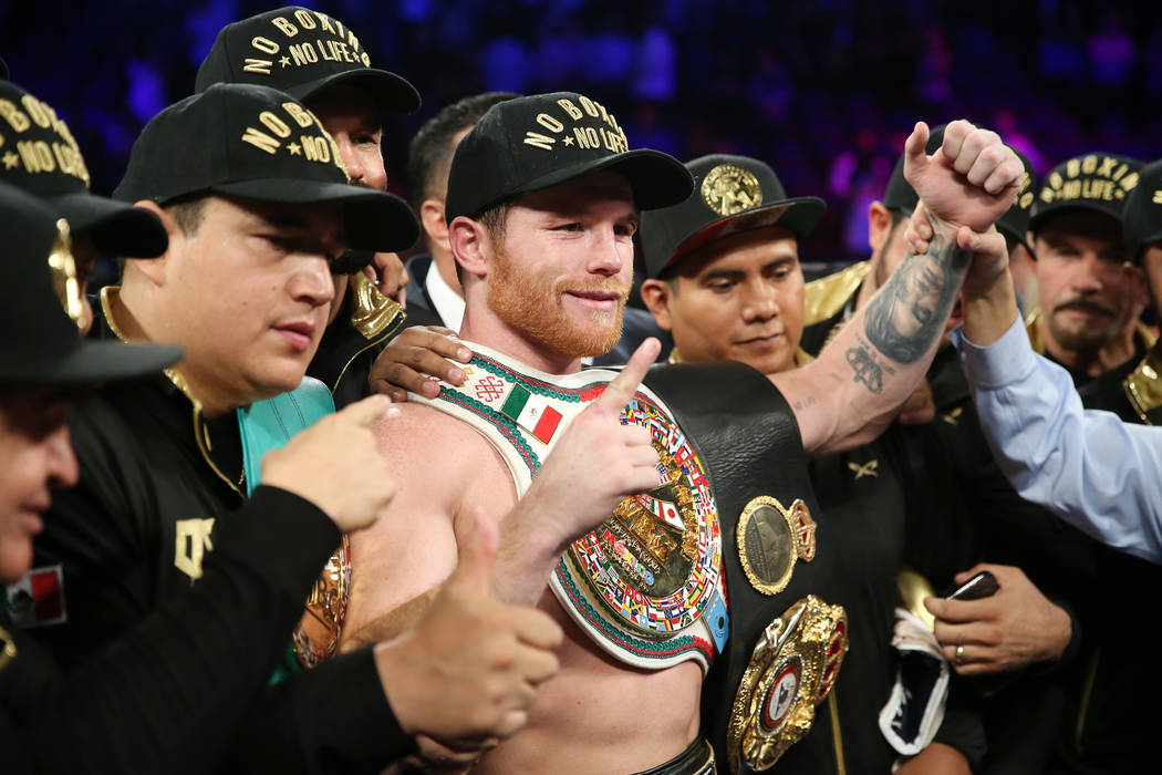 """Saul """"Canelo"""" Alvarez, center, celebrates his majority decision win against Gennady Golovkin in the WBC, WBA, IBO, RING middleweight title bout at T-Mobile Arena in Las Vegas, Saturday, ..."""