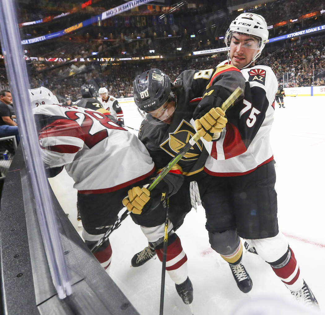 Golden Knights Tyler Wong (80) battles Arizona Coyotes Kyle Capobianco (75) during the first period of a preseason NHL hockey game at T-Mobile Arena in Las Vegas on Sunday, Sept. 16, 2018. Chase S ...