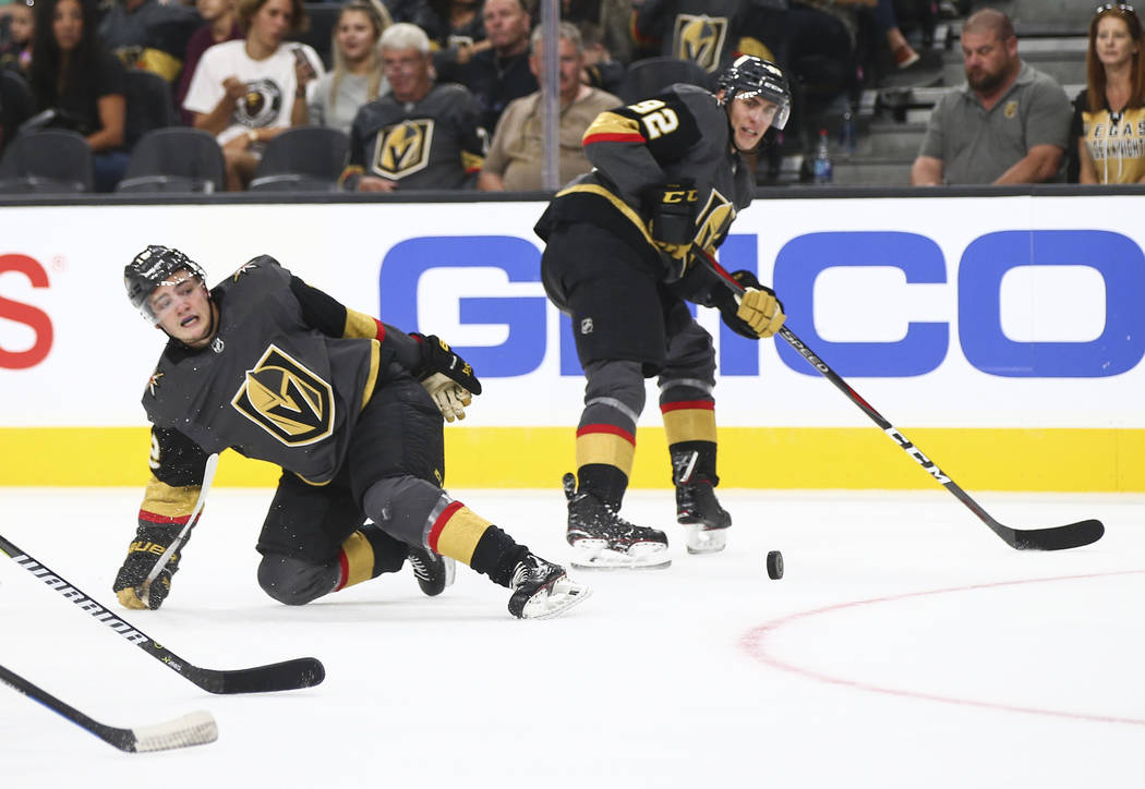 Golden Knights defenseman Erik Brannstrom (12) gets tripped up next to Golden Knights left wing Tomas Nosek (92) during the second period of a preseason NHL hockey game against the Arizona Coyotes ...