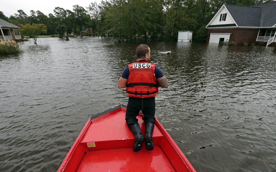 Petty Officer Second Class David Kelley patrols a flooded neighborhood in Lumberton, N.C., Sunday, Sept. 16, 2018, following flooding from Hurricane Florence. (AP Photo/Gerry Broome)
