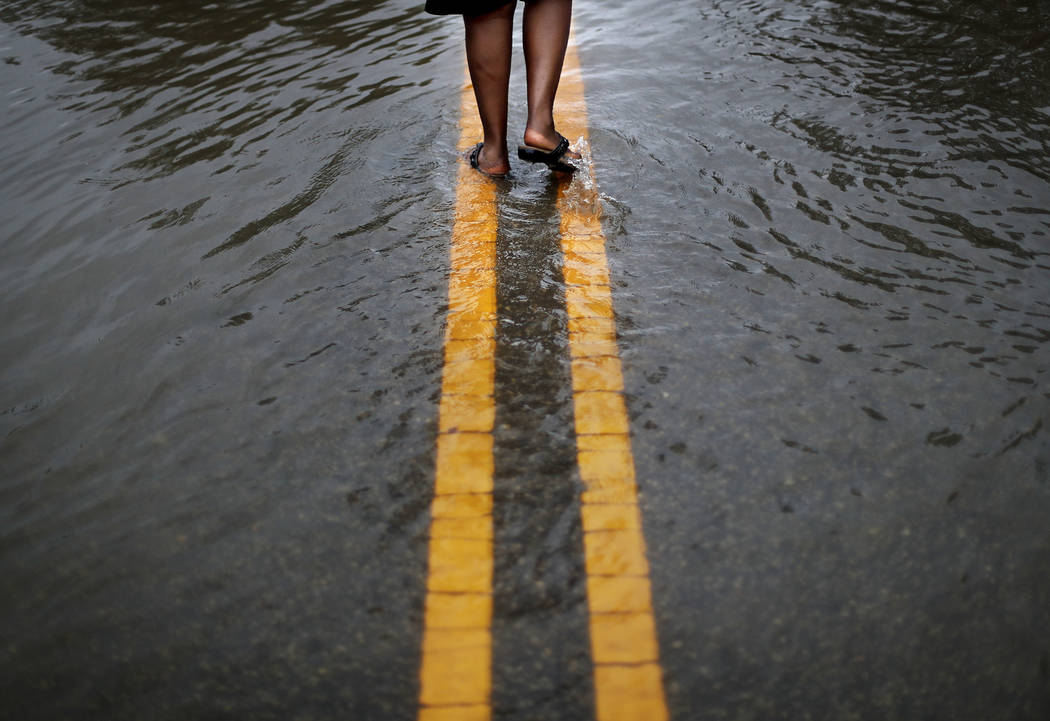 Helen McKoy walks down a flooded street in her neighborhood as Florence continues to dump heavy rain in Fayetteville, N.C., Sunday, Sept. 16, 2018. (AP Photo/David Goldman)