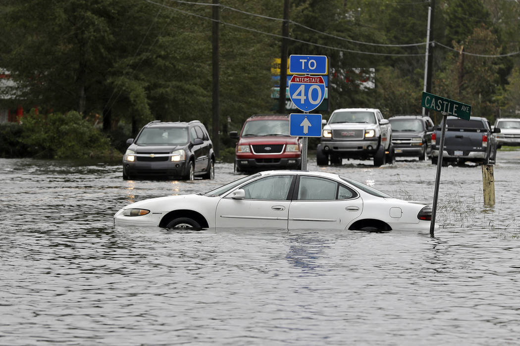 Cars try to navigate a flooded road leading to Interstate 40 in Castle Hayne, N.C., after damage from Hurricane Florence cut off access to Wilmington, N.C., Sunday, Sept. 16, 2018. (AP Photo/Chuck ...