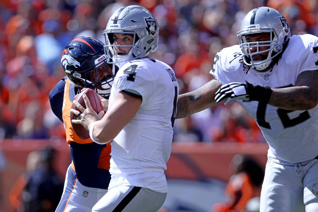Oakland Raiders offensive tackle Donald Penn (72) tries to hold off Denver Broncos linebacker Von Miller (58) as quarterback Derek Carr (4) looks for an open receiver during the first half of thei ...
