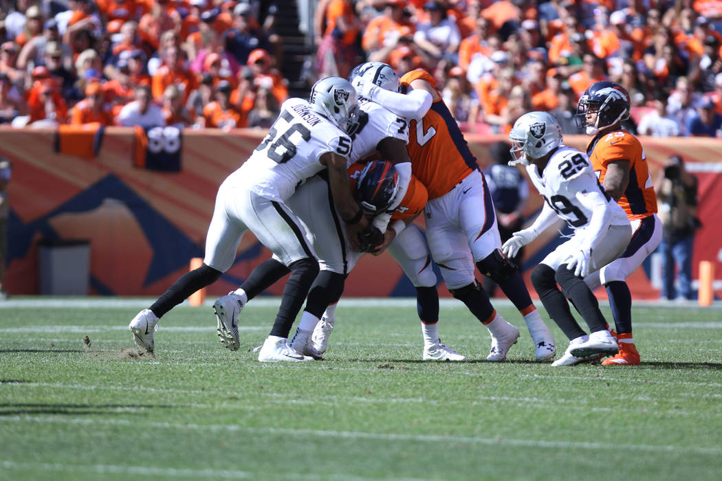 Oakland Raiders linebacker Derrick Johnson (56) and defensive tackle Maurice Hurst (73) sack Denver Broncos quarterback Case Keenum (4) during the first half of their NFL game in Denver, Colo., Su ...
