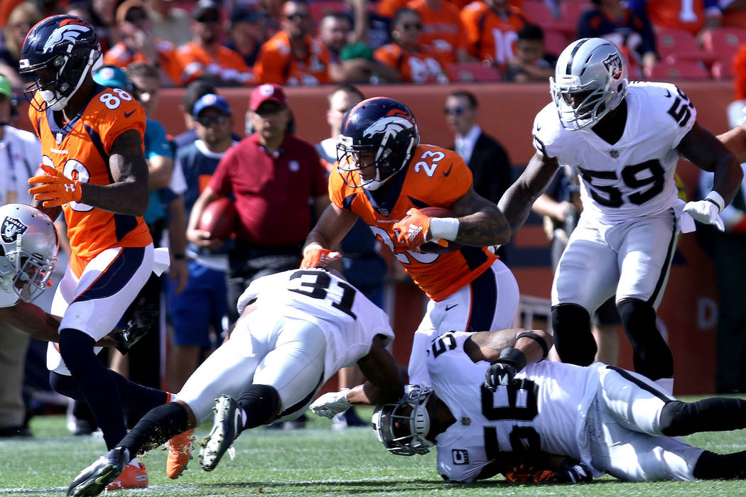 Denver Broncos running back Devontae Booker (23) runs with the football past Oakland Raiders defensive back Marcus Gilchrist (31), linebacker Derrick Johnson (56) and linebacker Tahir Whitehead (5 ...