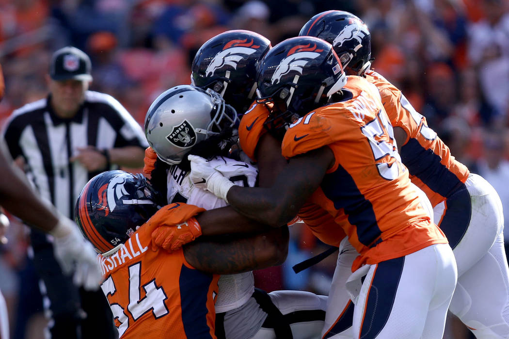 Oakland Raiders running back Marshawn Lynch (24) is tackled by Denver Broncos linebacker Brandon Marshall (54), linebacker Todd Davis (51) and others during the second half of their NFL game in D ...