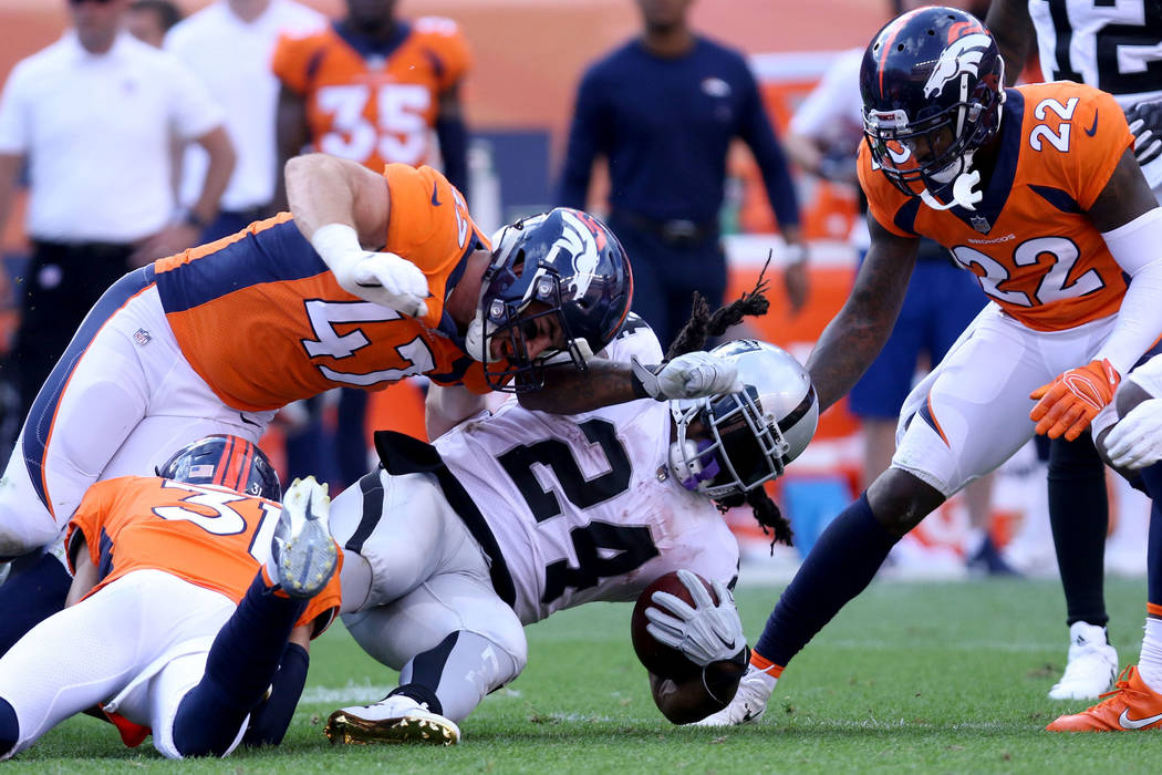 Oakland Raiders running back Marshawn Lynch (24)is tackled by Denver Broncos linebacker Josey Jewell (47) and defensive back Justin Simmons (31) during the second half of their NFL game in Denver, ...