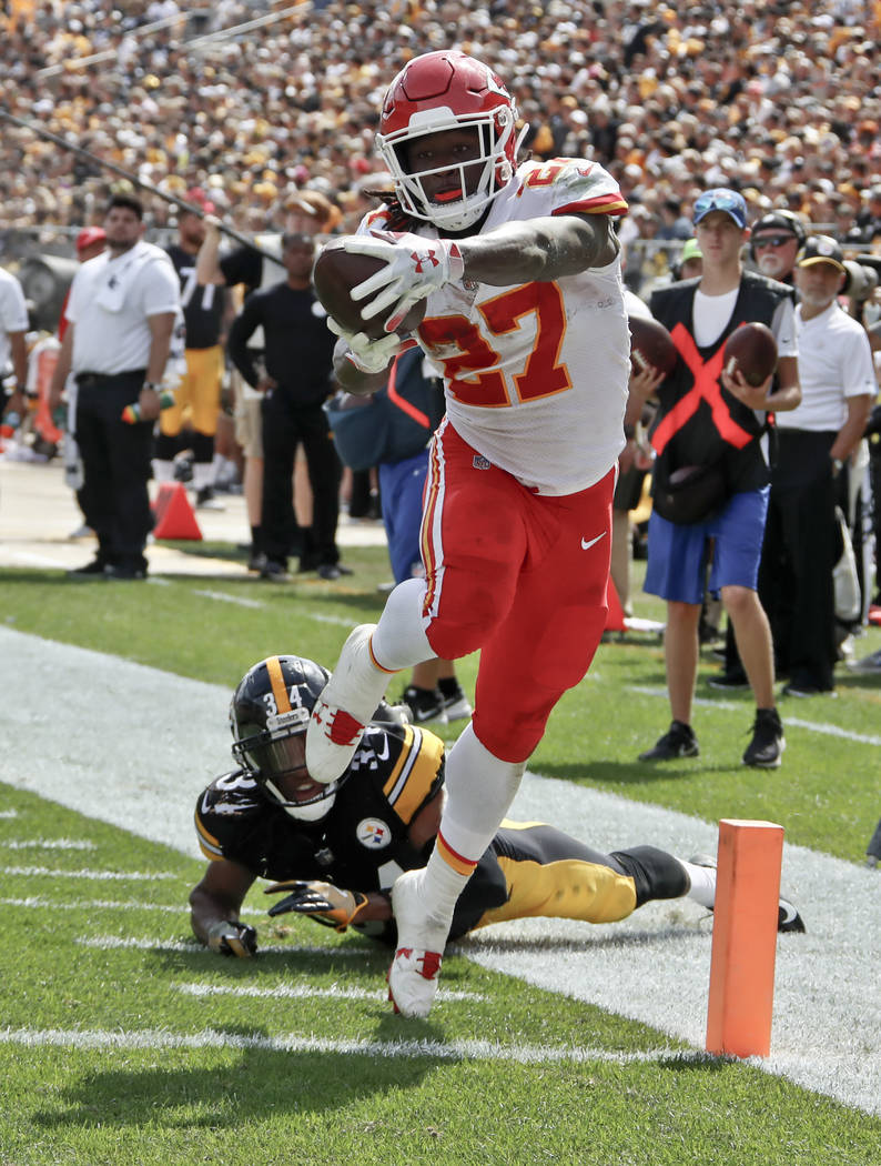 Kansas City Chiefs running back Kareem Hunt (27) gets away from Pittsburgh Steelers defensive back Terrell Edmunds (34) for a touchdown in the first half of an NFL football game against the Pittsb ...