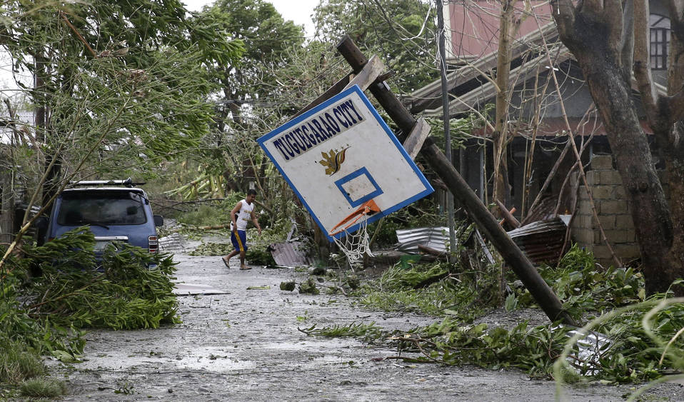 A resident walks beside a toppled basketball court after Typhoon Mangkhut barreled across Tuguegarao city, Cagayan province, northeastern Philippines, Saturday, Sept. 15, 2018. (AP Photo/Aaron Fa ...